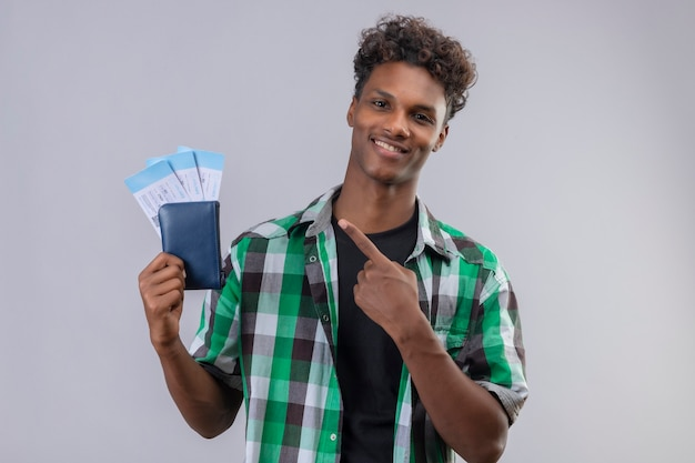 흰색 배경 위에 유쾌하게 긍정적이고 행복하게 미소를 그들에게 손가락으로 가리키는 항공 티켓을 들고 젊은 아프리카 계 미국인 여행자 남자 무료 사진