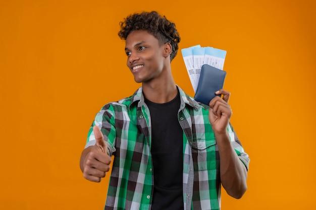 유쾌 하 고 긍정적이고 행복 하 게 웃 고 옆으로 엄지 손가락을 보여주는 항공 티켓을 들고 젊은 아프리카 계 미국인 여행자 남자 무료 사진