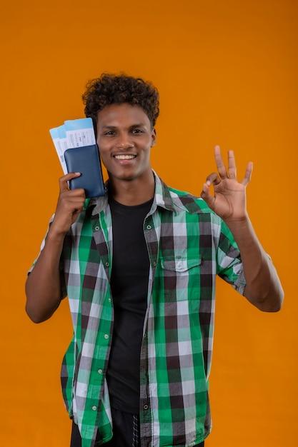 오렌지 배경 위에 서있는 확인 사인을하고 카메라를보고 유쾌하게 긍정적이고 행복하게 웃는 항공 티켓을 들고 젊은 아프리카 계 미국인 여행자 남자 무료 사진