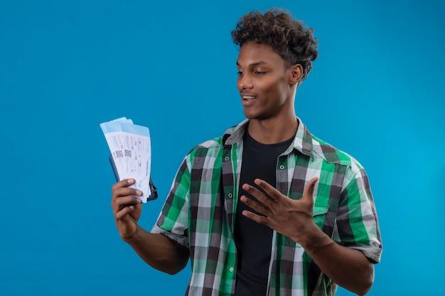 유쾌하게 긍정적이고 행복하게 웃는 항공권을 들고 젊은 아프리카 계 미국인 여행자 남자 티켓을보고 파란색 배경 위에 서 종료 무료 사진