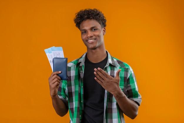 오렌지 배경 위에 서있는 카메라를보고 그의 손의 팔로 유쾌하게 긍정적이고 행복하게 제시 웃는 항공 티켓을 들고 젊은 아프리카 계 미국인 여행자 남자 무료 사진