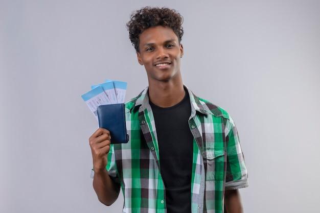 유쾌하고 긍정적이고 행복하게 웃는 항공권을 들고 젊은 아프리카 계 미국인 여행자 남자 무료 사진