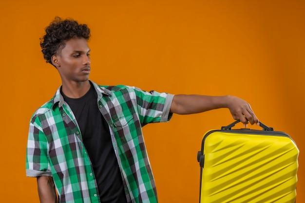 オレンジ色の背景の上に立って疑問を持っている顔に混乱した表情でそれを見てスーツケースを持って若いアフリカ系アメリカ人旅行者男 無料写真