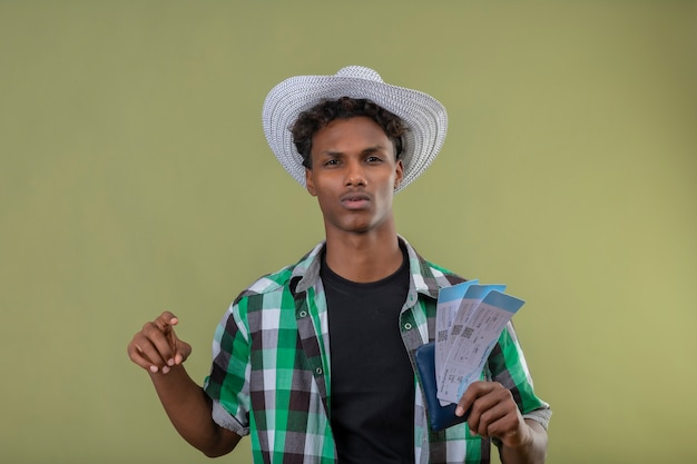 緑の背景の上に立って深刻な自信を持って式でカメラを見て航空券を保持している夏帽子の若いアフリカ系アメリカ人旅行者男 無料写真