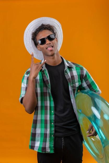 オレンジ色の背中にカメラ立って見て楽しい舌を突き出してロックサインをやっているインフレータブルリングを保持している黒いサングラスをかけている夏帽子の若いアフリカ系アメリカ人旅行者男 無料写真