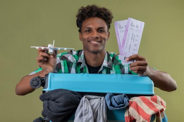 Молодой афро-американский путешественник, стоящий с чемоданом, полным одежды, держит авиабилеты и игрушечный самолет, глядя в камеру, улыбаясь счастливым и позитивным на зеленом фоне Бесплатные Фотографии