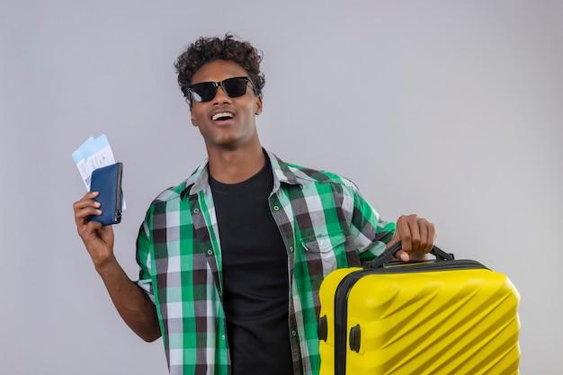 유쾌하고 긍정적이고 행복하게 웃는 항공 티켓을 들고 가방과 함께 검은 선글라스를 착용하는 젊은 아프리카 계 미국인 여행자 남자 무료 사진