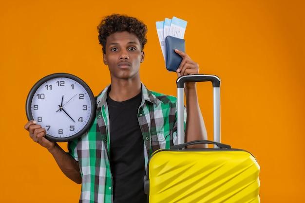 걱정 하 고 혼란 스 러 워 보이는 항공 티켓과 시계를 들고 가방을 가진 젊은 아프리카 계 미국인 여행자 남자 무료 사진