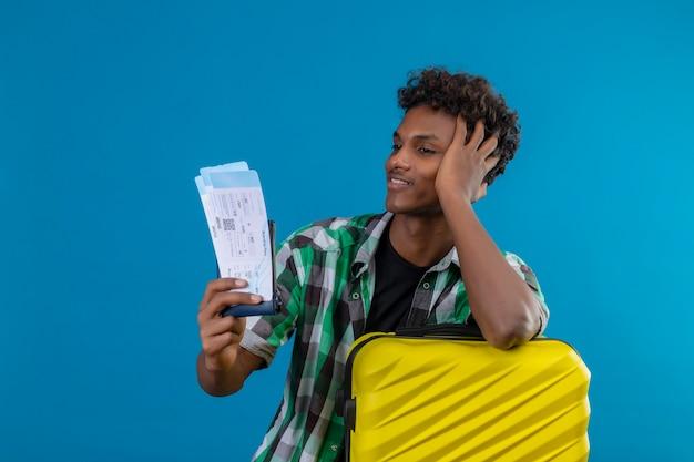 얼굴에 자신감이 미소로 그들을보고 항공 티켓을 들고 가방을 가진 젊은 아프리카 계 미국인 여행자 남자, 만족 무료 사진