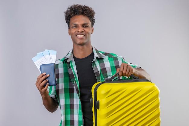 유쾌하고 긍정적이고 행복하게 웃는 항공 티켓을 들고 가방을 가진 젊은 아프리카 계 미국인 여행자 남자 무료 사진