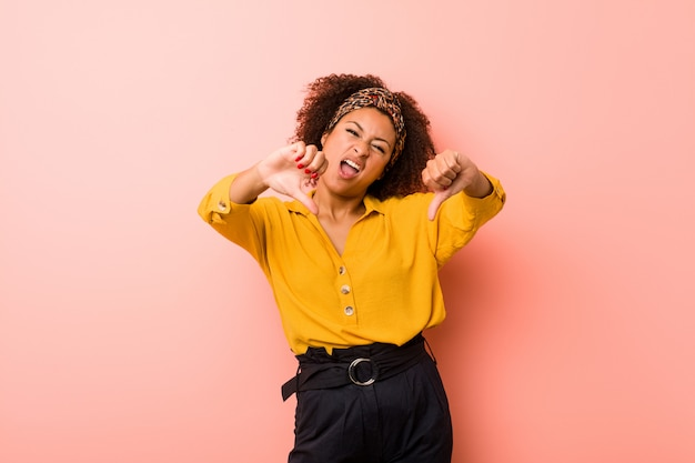 親指を示すと嫌悪感を表現するピンクの壁に若いアフリカ系アメリカ人女性。 Premium写真
