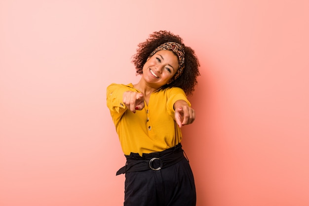 Young african american woman against a pink  cheerful smiles pointing to front. Premium Photo