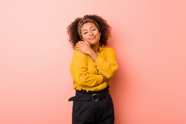 Young african american woman against a pink  hugs, smiling carefree and happy. Premium Photo