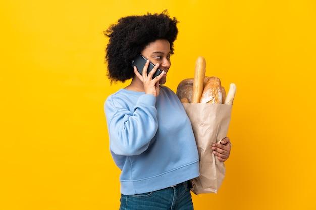 Молодая афроамериканская женщина покупает что-то хлеб, изолированные на желтом фоне, разговаривая с кем-то по мобильному телефону Premium Фотографии