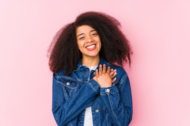 Young african american woman has friendly expression, pressing palm to chest. love concept. Premium Photo