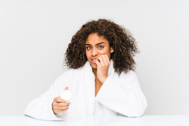 Молодая афро-американская женщина, держащая увлажняющий крем, кусая ногти, нервничает и очень тревожится. Premium Фотографии