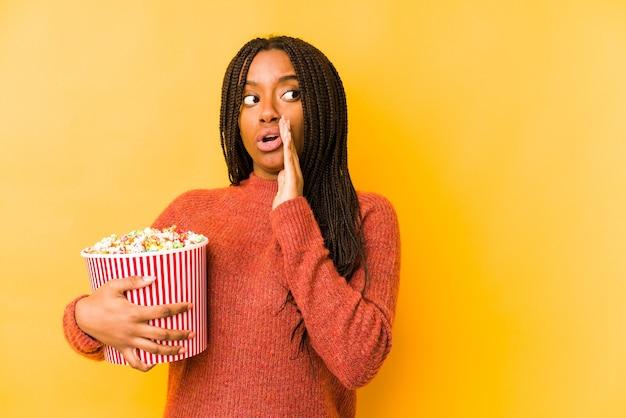 Молодая афроамериканка, держащая в руках попкорн, рассказывает секретные горячие новости о торможении и смотрит в сторону Premium Фотографии