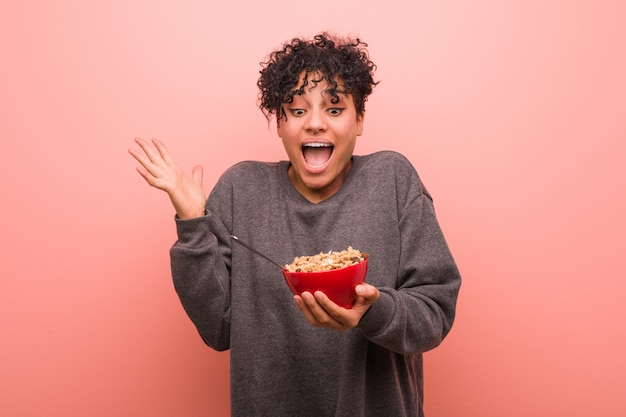 Young african american woman holding a cereal bowl celebrating a victory or success Premium Photo