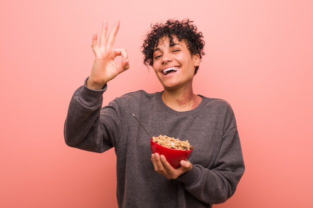Young african american woman holding a cereal bowl cheerful and confident showing ok gesture. Premium Photo