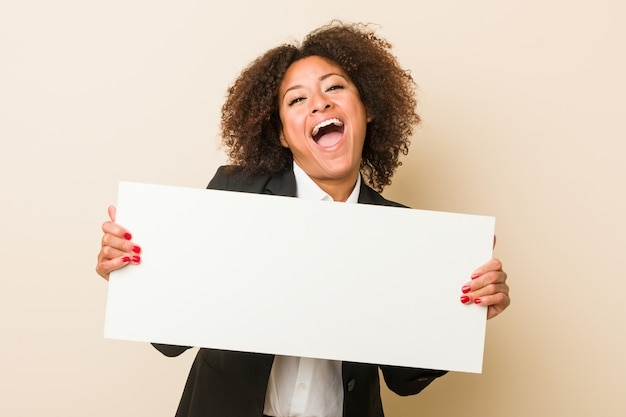 Young african american woman holding a placard celebrating a victory or success Premium Photo