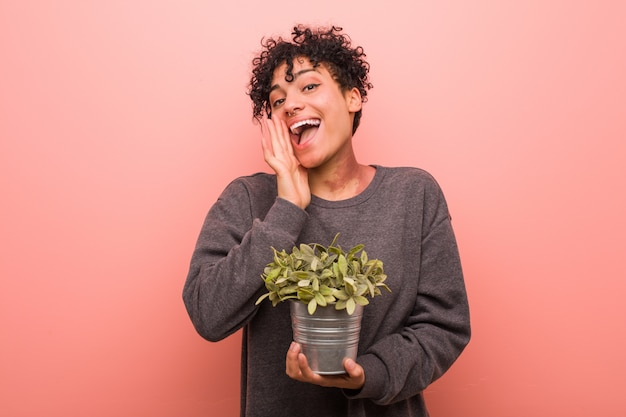 Young african american woman holding a plant shouting excited to front. Premium Photo