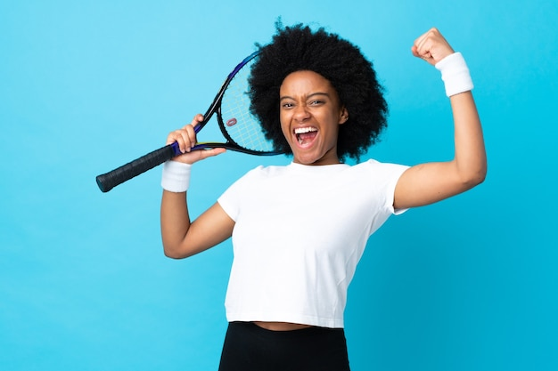 Young african american woman isolated on blue background playing tennis and celebrating a victory Premium Photo