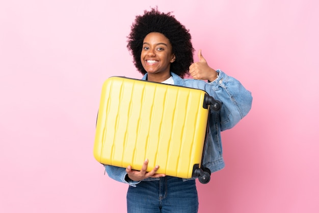 Young african american woman isolated on pink background in vacation with travel suitcase and with thumb up Premium Photo