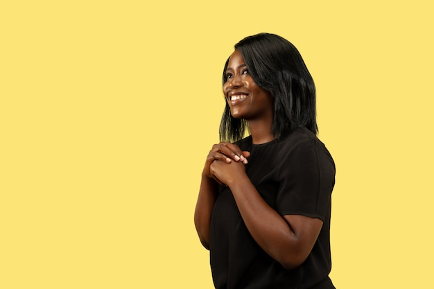 Young african-american woman isolated on yellow wall, facial expression. beautiful female half-length portrait. concept of human emotions, facial expression. standing and smiling. Free Photo