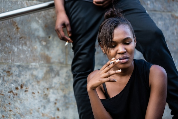 Young african american woman and man smoking outdoors in the cit Premium Photo