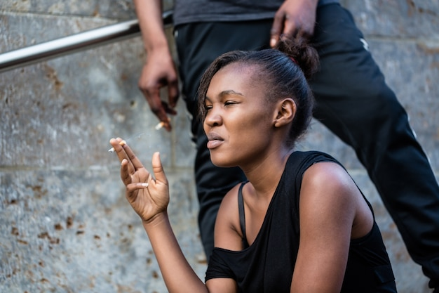 Young african american woman and man smoking outdoors in the city Premium Photo