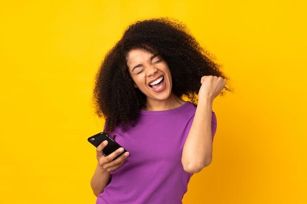勝利の位置に電話で壁を越えて若いアフリカ系アメリカ人女性 Premium写真
