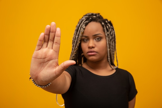Young african american woman shown hand on sign for them to stop with racial prejudice. Premium Photo
