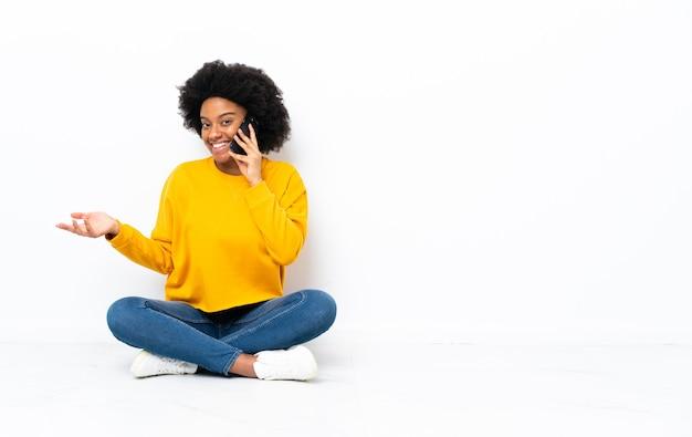 Молодая афроамериканская женщина сидит на полу, разговаривает с кем-то по мобильному телефону Premium Фотографии