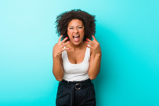 Young african american woman upset screaming with tense hands. Premium Photo
