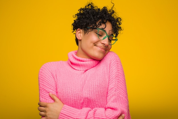 Young african american woman wearing a pink sweater hugs, smiling carefree and happy. Premium Photo