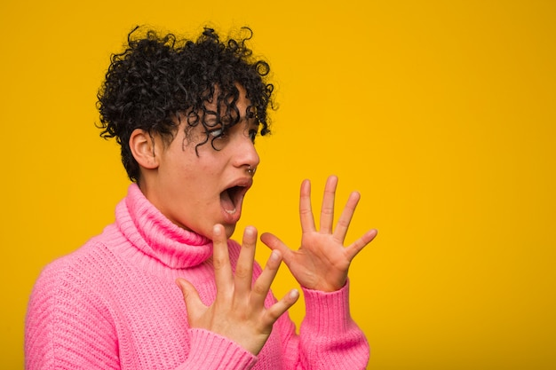 Young african american woman wearing a pink sweater shouts loud, keeps eyes opened and hands tense. Premium Photo