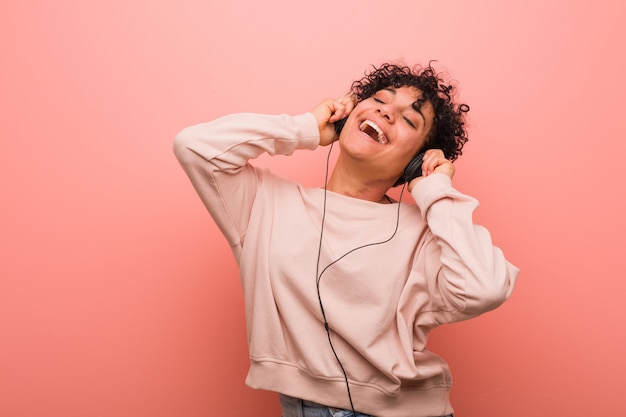 Young african american woman with a birthmark dancing and listening to music with a headphone Premium Photo