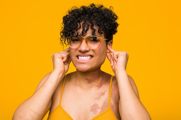 Young african american woman with skin birth mark covering ears with hands. Premium Photo