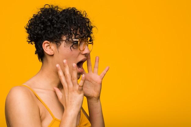 皮膚の出生マークを持つ若いアフリカ系アメリカ人女性は大声で叫ぶ、目を開いたまま、手が緊張します。 Premium写真