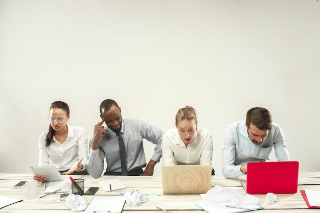 若いアフリカと白人の男性と女性がオフィスに座っているとラップトップに取り組んでいます。ビジネス、感情、チーム、チームワーク、職場、リーダーシップ、会議のコンセプト。同僚のさまざまな感情 無料写真