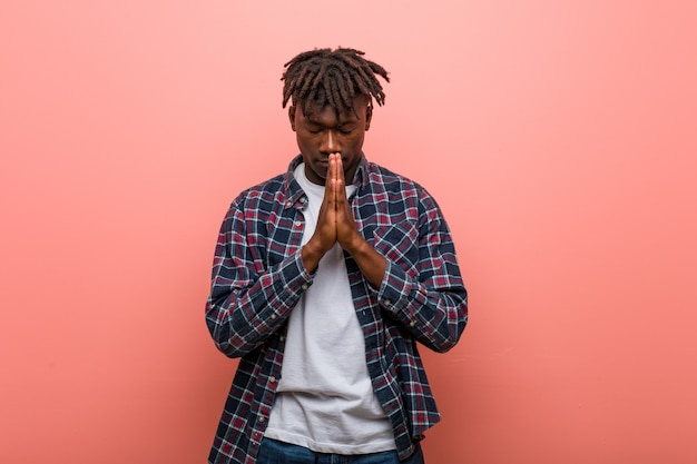 Young african black man holding hands in pray near mouth, feels confident. Premium Photo