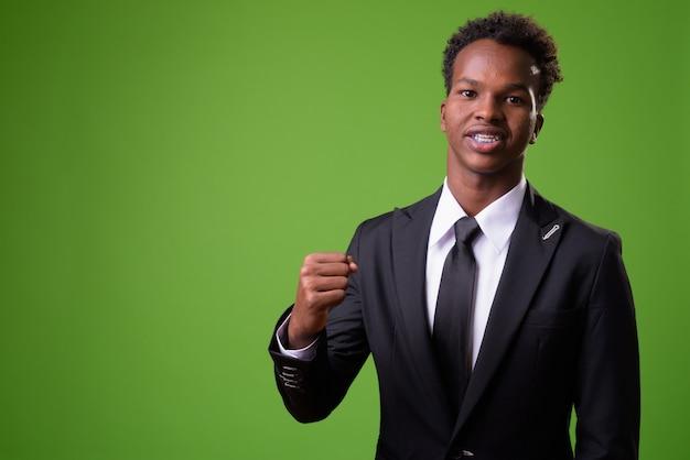 緑の壁に対して若いアフリカの実業家 Premium写真