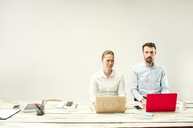 Giovani uomini e donne africani e caucasici seduti in ufficio e lavorando su laptop. il business, le emozioni, la squadra, il lavoro di squadra, il posto di lavoro, la leadership, il concetto di riunione. diverse emozioni dei colleghi Foto Gratuite