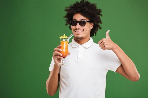 カクテルを飲みながら若いアフリカの巻き毛の男。 Premium写真