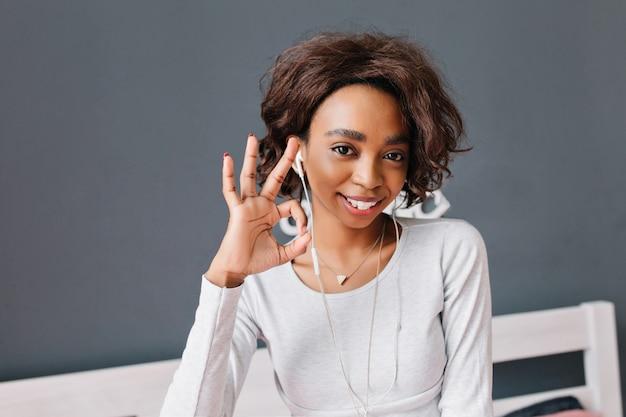 笑顔、大丈夫、イヤホンで音楽を聴く、家で楽しい時間を過ごすアフリカの少女。白い家具と灰色の壁。長袖のライトグレーのtシャツを着ています。 無料写真