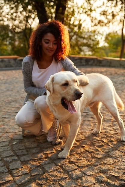 座っていると公園で犬を抱いてカジュアルな服装の若いアフリカ女性 無料写真