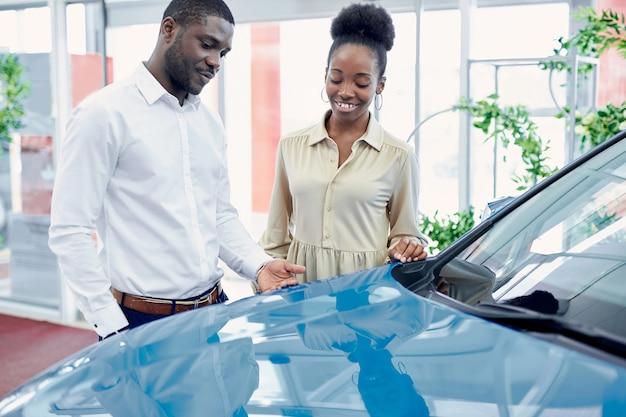 若いアフリカ人男性がディーラーで車について妻の意見を尋ねる Premium写真
