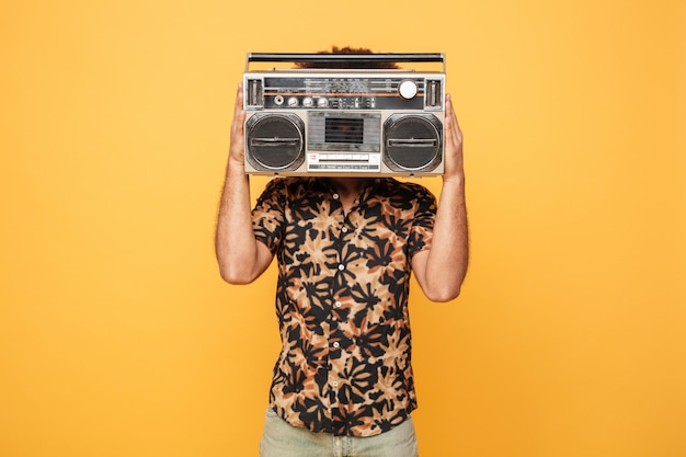 Young african man covering face with tape recorder Free Photo