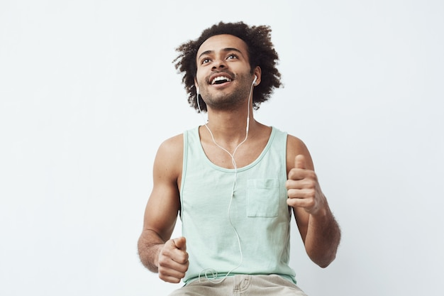 Young african man listening to music in headphones dancing Free Photo