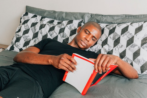 A young african man lying on bed reading book Free Photo